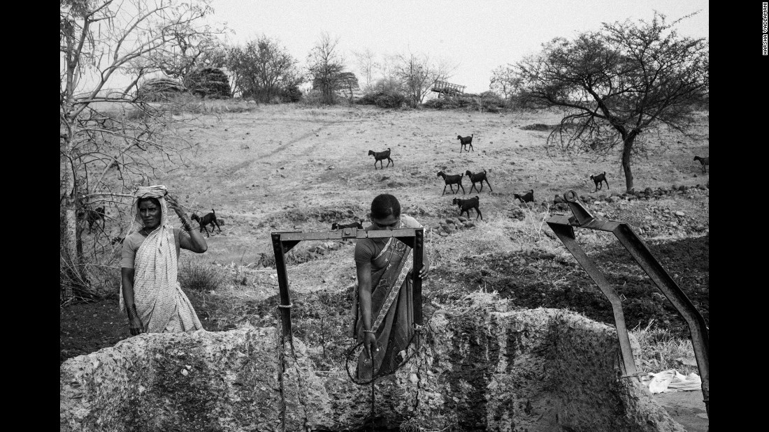 Women in Karigaon, India, draw water from a well that is replenished once a day with water from tankers.