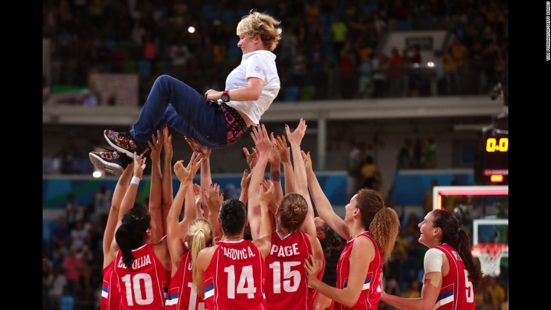 The Serbian basketball team celebrates with their coach, Marina Maljkovic, after defeating France 70-63 in the bronze medal match.