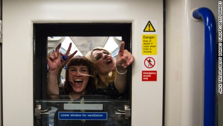 Passengers on board the Night Tube wave and cheer through a window in a carriage along the Victoria line on August 20, 2016 in London, England.