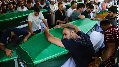 A mourner leans on a coffin at a funeral for victims of the Gaziantep blast.