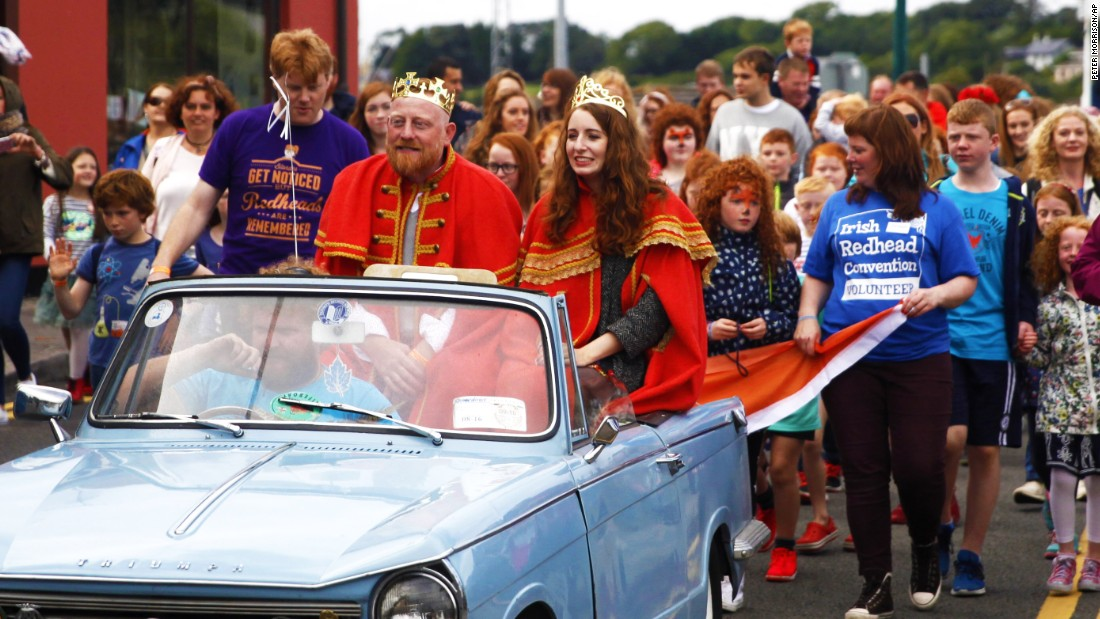 "Newly-crowned ""king"" and ""queen"" of the redheads Emma Ni Chearuil and Alan O' Neill ride in a car at their coronation parade. Over 40 ""ginger-themed"" events took place over the three-day event -- including redhead seminars, speed dating and prizes for the most freckles per square inch, according to the convention's website."