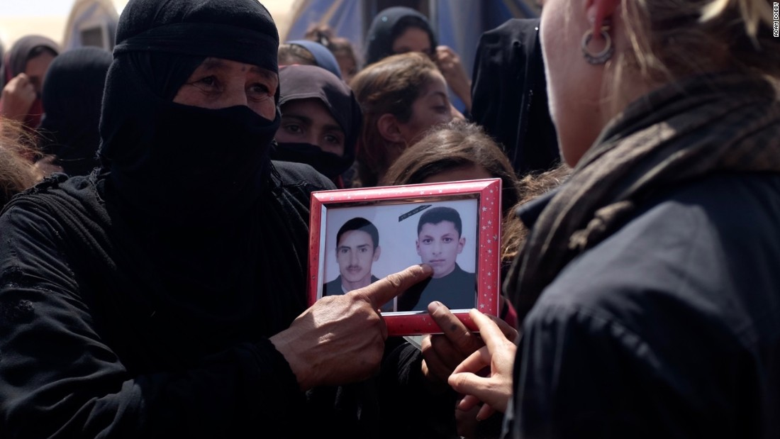 Iraqi mother Piswa Treish holds a picture of her son (right) who was killed by ISIS.