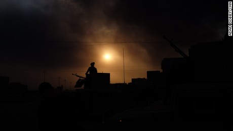 An Iraqi soldier stands guard on the outskirts of Qayyarah, under apocalyptic skies filled with smoke.