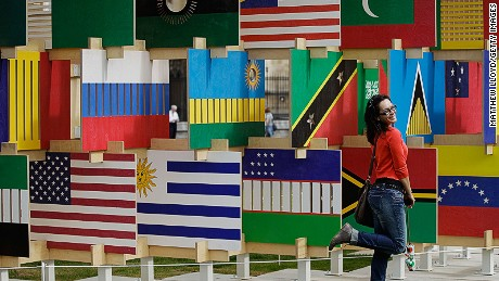LONDON, ENGLAND - AUGUST 02: Tourists take pictures in front of The House of Flags installation in Parliament Square on August 2, 2012 in London, England. 206 panels displaying all the flags of the nations participating in the 2012 Olympics and Paralympics, have been combined together into a jigsaw 'house'. (Photo by Matthew Lloyd/Getty Images)
