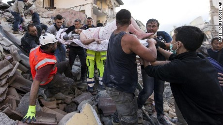 A woman is pulled from the rubble following an earthquake in Amatrice, Italy.