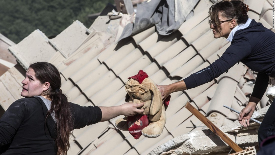 Two women pass along a stuffed toy in Amatrice on August 24.