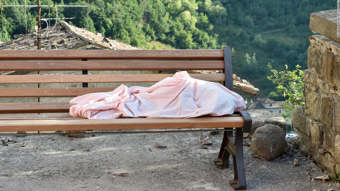 The body of a unidentified child lies on a bench in Arquata del Tronto on August 24.
