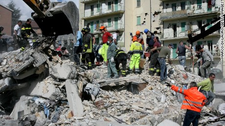 Rescue workers search for bodies amongst the rubble of a destroyed building on April 6, 2009 in L'Aquila, Italy. The 6.3 magnitude earthquake tore through central Italy, devastating historic mountain towns, killing at least 90 people and injuring some 1500.