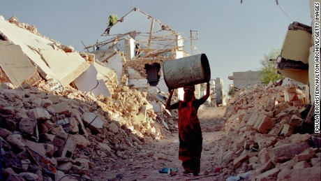 A woman walks to her tent on the outskirts of Bhuj, India, after an earthquake left tens of thousands homeless.