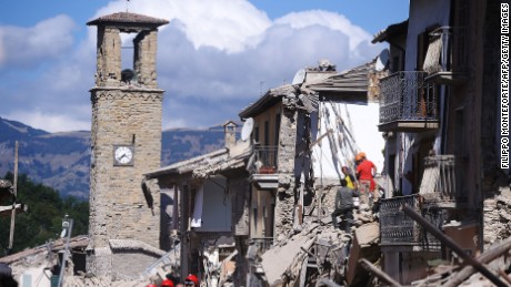 Firemen and rescuers inspect damaged buildings in Amatrice.