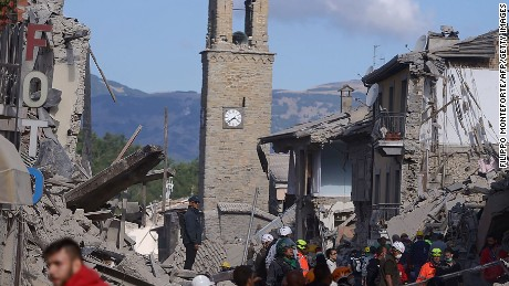 Rescuers and firemen inspect the rubble of buildings  in Amatrice on August 24, 2016 after a powerful earthquake rocked central Italy. 