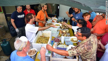 Emergency workers and earthquake survivors get food at a field kitchen in Amatrice on Thursday.