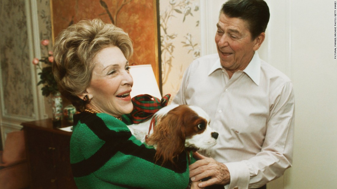President Ronald Reagan presents first lady Nancy Reagan with a King Charles spaniel named Rex as an early Christmas present at their suite in a New York City hotel on December 6, 1985.