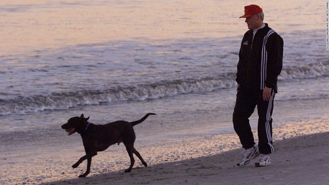 Clinton walks Buddy along the beach during sunset in Hilton Head, South Carolina, on December 30, 1992.