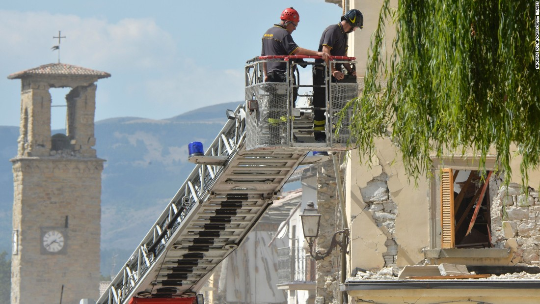 Firefighters inspect a damaged building from the elevated platform of a firetruck in Amatrice on August 26. Amatrice has been the hardest-hit town, with more than 200 killed there.