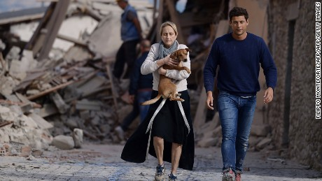 A woman holds a dog as she and a man hurry past rubble in Amatrice.