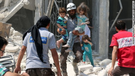 A Syrian rescue worker carries children in the Maadi district of eastern Aleppo after regime aircrafts reportedly dropped explosive-packed barrel bombs on August 27, 2016.       At least 15 civilians were reported killed when two bombs fell several minutes apart, near a tent where people were receiving condolences for those killed this week.    / AFP / AMEER ALHALBI        (Photo credit should read AMEER ALHALBI/AFP/Getty Images)