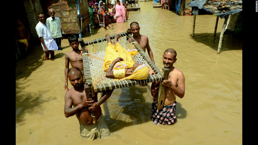 People transfer a woman to a safe area after flooding in Danapur, India, on Sunday, August 21.