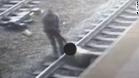 Man fights to stay on tracks as train roars in