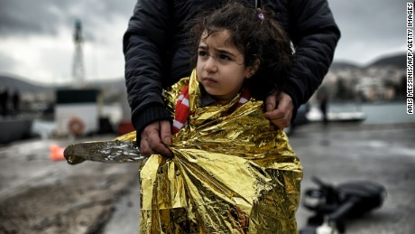 A father stands with his daughter wrapped in a thermal blanket as refugees and migrants arrive to the port of the northern island of Lesbos in Mytilene after crossing the Aegean sea from Turkey on February 19, 2016.