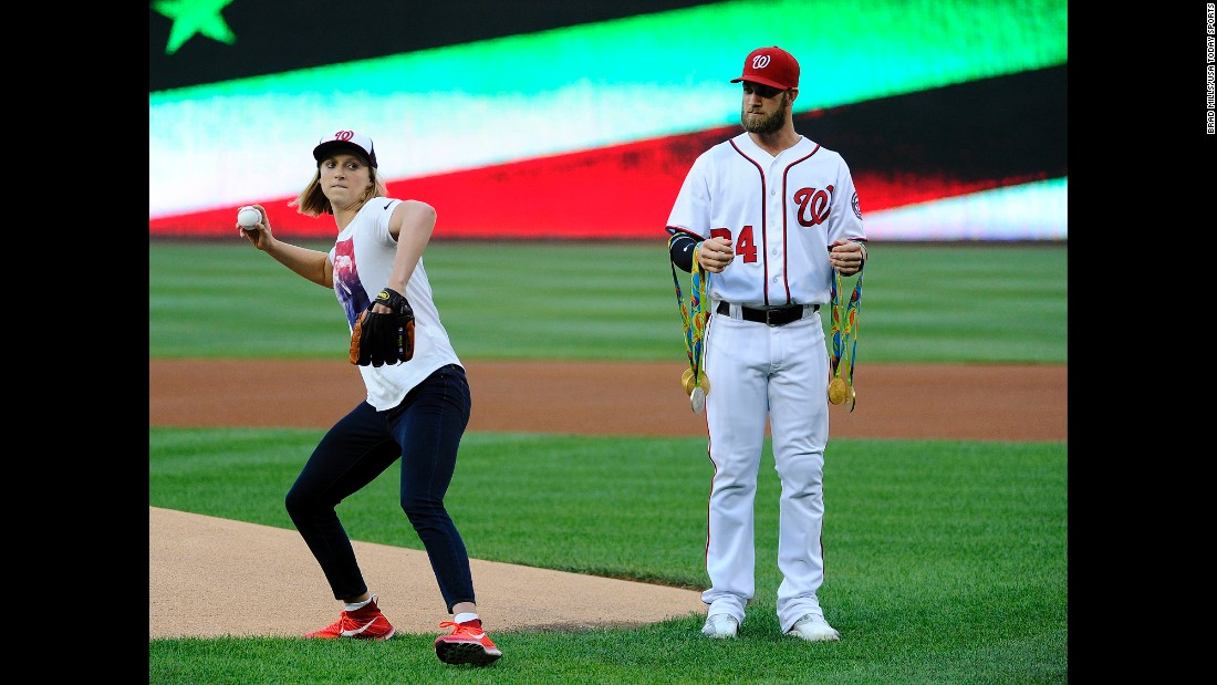 Baseball star Bryce Harper holds Katie Ledecky's Olympic medals as the swimmer throws out the first pitch before a Washington Nationals game on Wednesday, August 24.