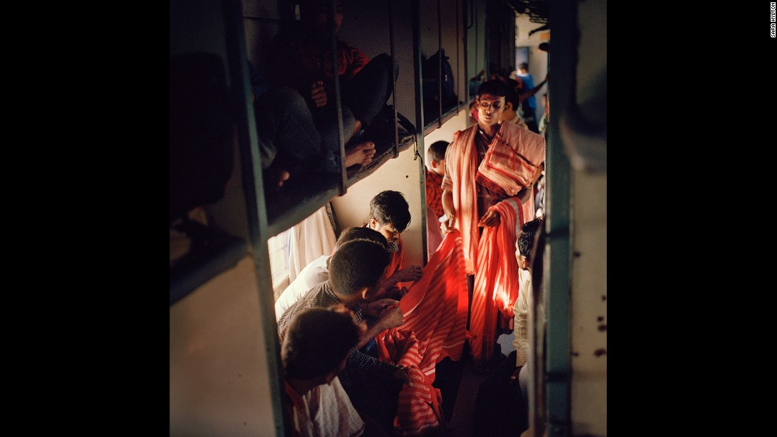 A vendor shows textiles to passengers on India's longest train, the Vivek Express.