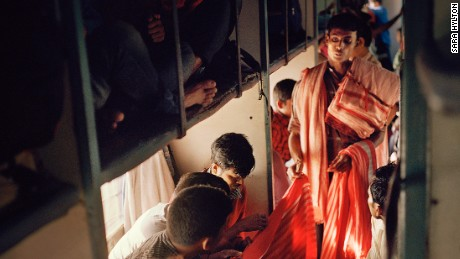 An unauthorized vendor shows textiles to passengers on India's longest train, the Vivek Express running over the length of 5 days. There are approximately 10 million illegal vendors operating around India, and many make a living by selling their goods in urban areas and around bus and railway stations. Photographer: Sara Hylton