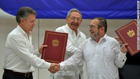 """Colombia's President Juan Manuel Santos (L) and Timoleon Jimenez, aka """"Timochenko"""" (R), head of the FARC leftist guerrilla, shake hands accompanied by Cuban President Raul Castro (C) during the signing of the peace agreement in Havana on June 23, 2016. Colombia's government and the FARC guerrilla force signed a definitive ceasefire Thursday, taking one of the last crucial steps toward ending Latin America's longest civil war. / AFP / ADALBERTO ROQUE        (Photo credit should read ADALBERTO ROQUE/AFP/Getty Images)"""