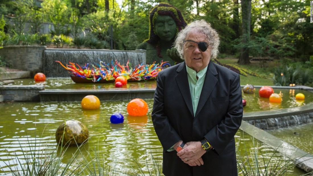 "Artist Dale Chihuly's latest show at the Atlanta Botanical Garden features 19 installations throughout the 30-acre garden. ""Fiori Boat and Niijima Floats"" is behind him at the base of the Earth Goddess in the Cascades Garden."