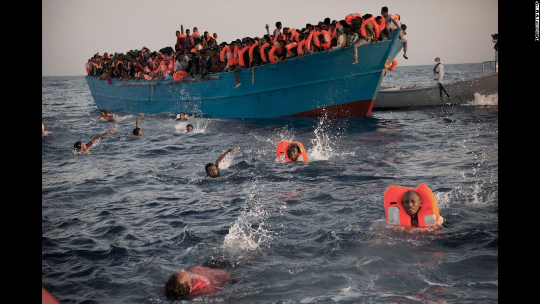 Migrants, most of them from Eritrea, jump into the Mediterranean from a crowded wooden boat during a rescue operation about 13 miles north of Sabratha, Libya, in August 2016.