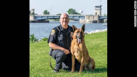 "Officer Fred Laitinen kneels beside his canine partner ""Cops"". Courtesy Eric Jaeger"