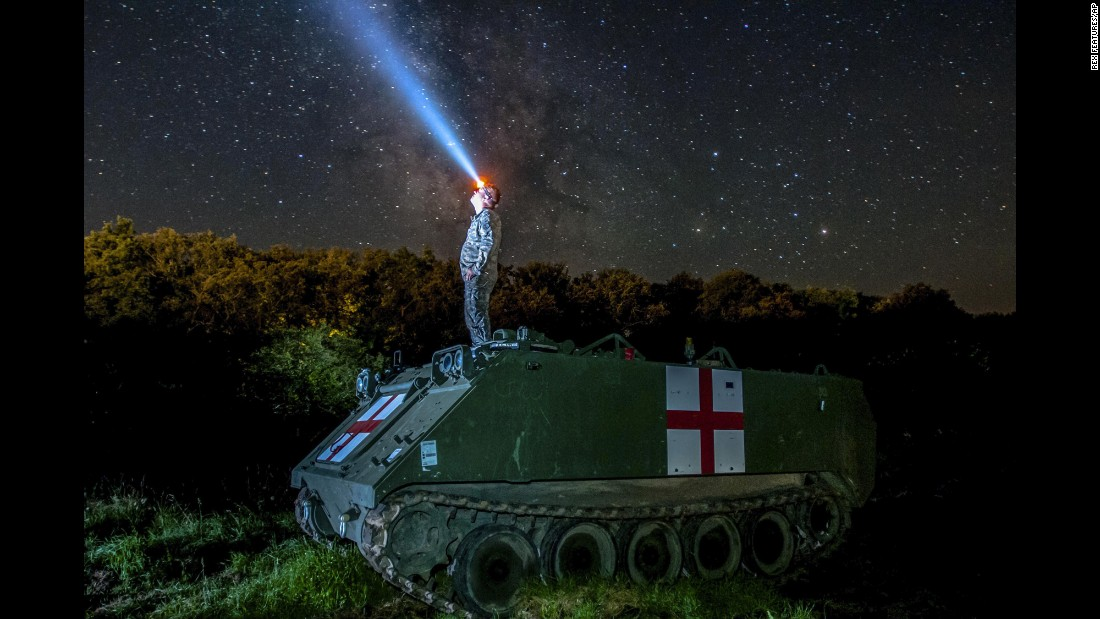 U.S. Army Pfc. Dylan Scott watches the night sky on top of a medical evacuation vehicle in Cincu, Romania, on Wednesday, August 3. He was taking part in a training exercise involving personnel from 10 nations.