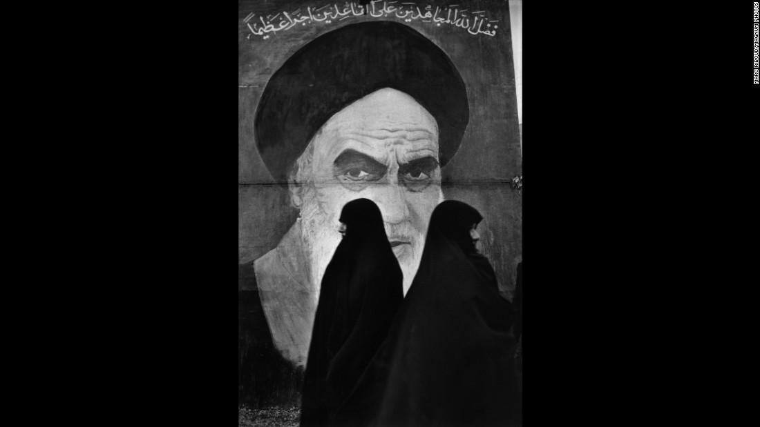 Women in Tehran, Iran, walk in front of a mural of Ayatollah Ruhollah Khomeini.