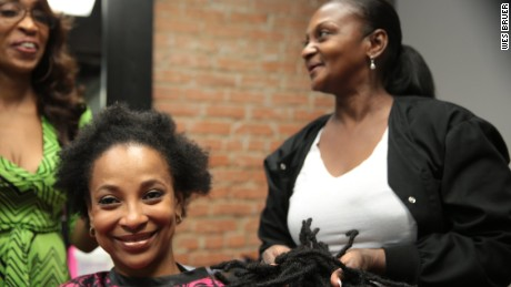 Sharanda Jones laughs with her sister, Sherena, after cutting off her dreadlocks upon her release.