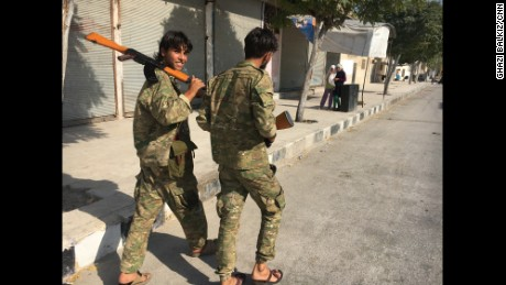 Two Free Syrian Army soldiers stroll down the main street of Jarablus after the city was liberated from ISIS.