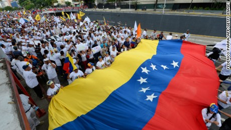 Opposition protesters unfurl a Venezuelan flag at a protest in Caracas.