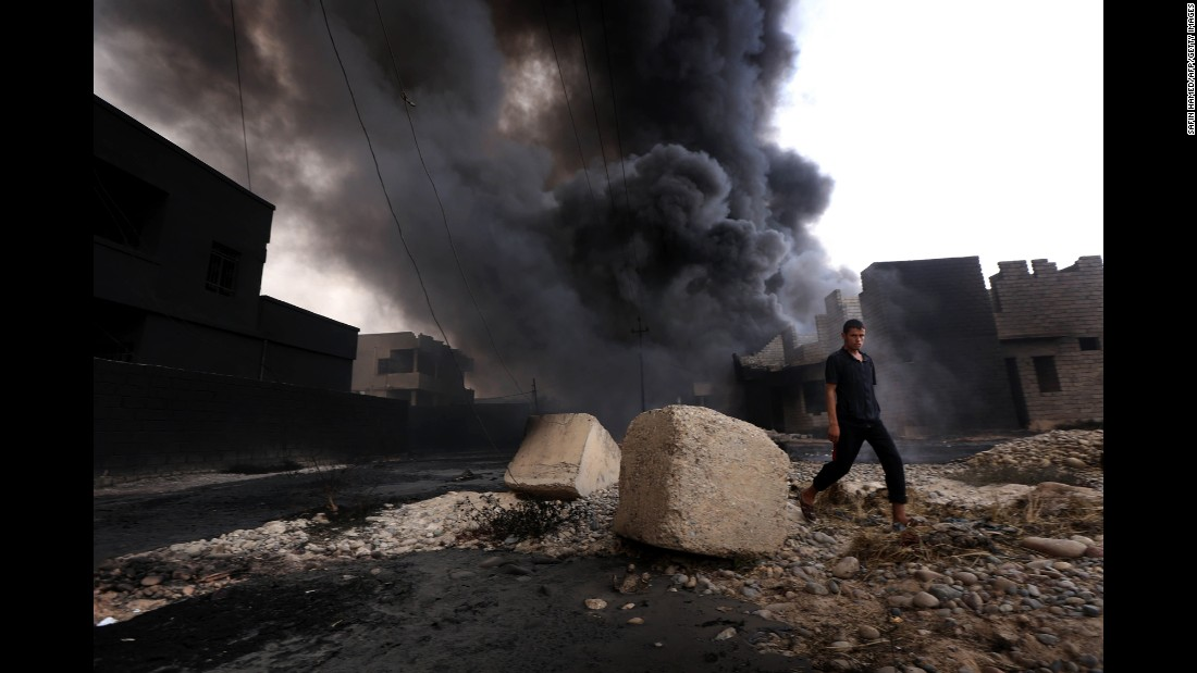 A man walks near smoke billowing from oil wells that were set ablaze by ISIS before Iraqi forces pushed the militants out of Qayyarah, Iraq, on Tuesday, August 30.