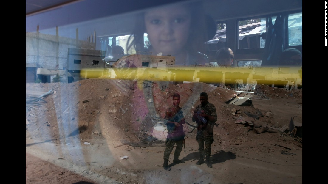 "Syrian troops are reflected on the window of a bus as it carries people out of the town of Daraya on Friday, August 26. <a href=""http://www.cnn.com/2016/08/26/middleeast/syria-daraya-evacuation/"" target=""_blank"">An evacuation agreement </a>reached between the Syrian government and rebels gave thousands of civilians safe passage out of the besieged Damascus suburb, the state-run Syrian Arab News Agency reported."