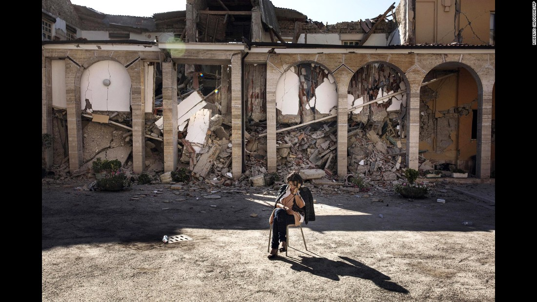 "A woman sits in a convent courtyard in Amatrice, Italy, on Friday, August 26, two days after <a href=""http://www.cnn.com/2016/08/24/europe/gallery/italy-earthquake/index.html"" target=""_blank"">a 6.2-magnitude earthquake.</a>"