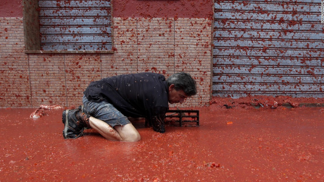 "A man unblocks a drain as tomato juice floods the streets of Bunol, Spain, during the annual <a href=""http://www.cnn.com/2015/08/27/travel/spain-la-tomatina-2015/"" target=""_blank"">Tomatina tomato fight</a> on Wednesday, August 31."