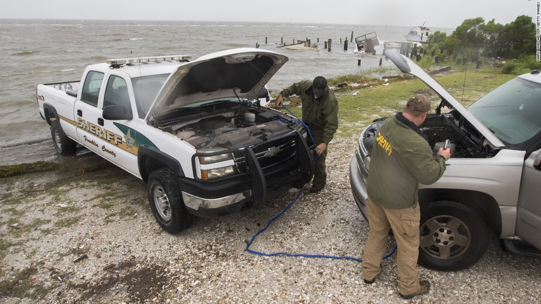 Sgt. Andy Pace and Lt. Allen Ham of the Franklin County Sheriff's Department jump-start one of their vehicles as Hermine approaches on September 1.