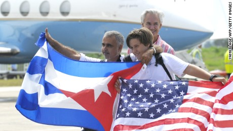 Passengers arriving at the airport of Santa Clara, Cuba on August 31, 2016 on the first commercial flight between the United States and Cuba since 1961, wave Cuban and US flags.