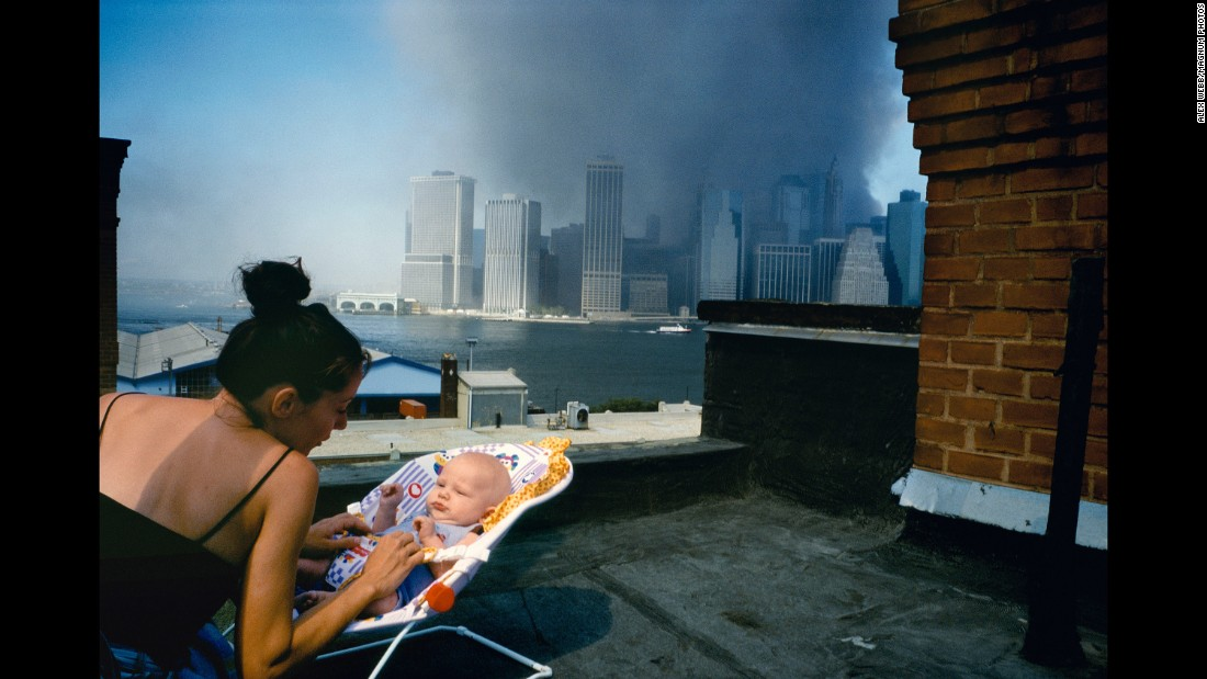 "A mother gently tends to her baby on a Brooklyn rooftop as smoke envelops lower Manhattan. ""There's some sense that, 'Well, this is the world he is coming into,'"" Alex Webb says."