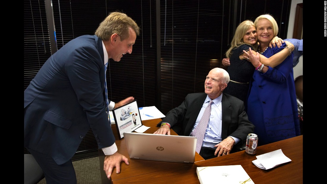"U.S. Sen. John McCain, seated, celebrates <a href=""http://www.cnn.com/2016/08/30/politics/john-mccain-debbie-wasserman-schultz-marco-rubio-primary/"" target=""_blank"">his Republican primary win</a> with fellow Sen. Jeff Flake as their two wives, Cheryl Flake and Cindy McCain, hug in Phoenix on Tuesday, August 30. McCain is seeking his sixth term in Arizona."