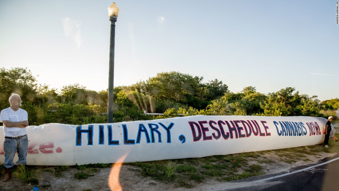"Protesters stand on the side of the road with an inflatable marijuana cigarette as a motorcade carries Hillary Clinton to a fundraiser in Southampton, New York, on Sunday, August 28. The Democratic presidential nominee <a href=""http://www.cnn.com/2015/11/07/politics/hillary-clinton-marijuana/"" target=""_blank"">has said she wants to downgrade marijuana as a Schedule 1 substance</a> so that more people can do research on its medical benefits. Marijuana is currently categorized by the Drug Enforcement Administration as a Schedule 1 drug, the highest categorization for drugs ""with no currently accepted medical use and a high potential for abuse."""