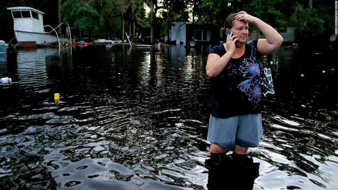 Lynne Garrett speaks to loved ones as she surveys damage outside of her home in St. Marks, Florida, on Friday, September 2.