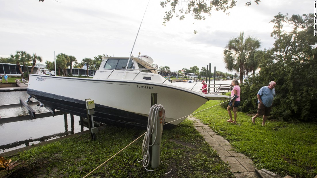 People check damage to a boat in their neighborhood in Shell Point Beach, Florida.