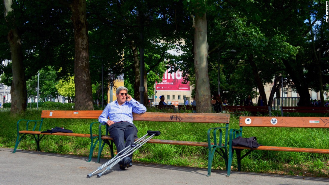 Kerry, on a park bench near the Imperial Hotel in Vienna, places a call to the president of the Dominican Republic in 2015. He needed crutches after breaking his leg in a May 2015 bike accident in France.