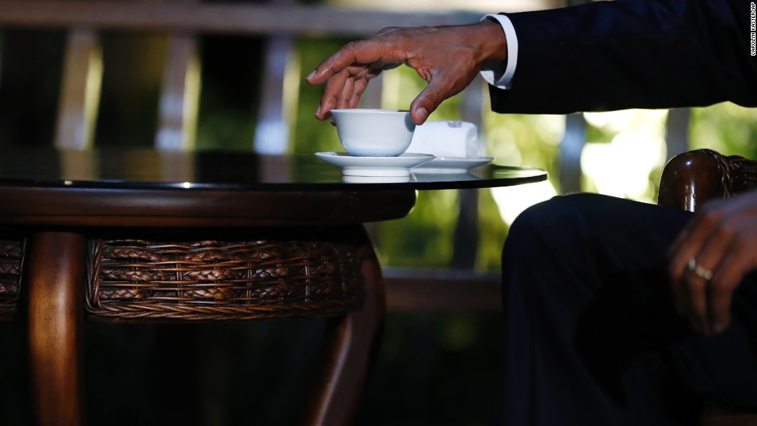President Barack Obama reaches for his cup as he drinks tea with Chinese President Xi Jinping in a pavilion at West Lake State Guest House in Hangzhou in eastern China's Zhejiang province on Saturday, September 3.
