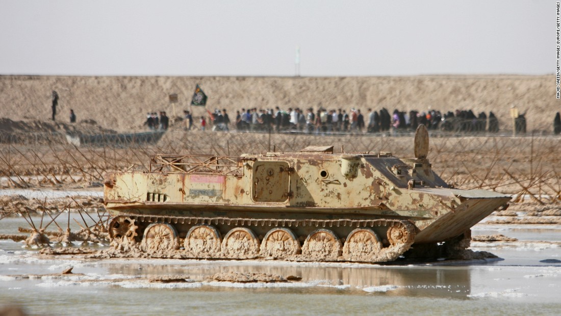 An estimated one million people lost their lives during the war between Iran and Iraq. In this photo taken on the Iran-Iraq border in 2007, Iranians walk past a destroyed tank on their way to pay respects at a memorial site.